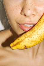 Woman Holding Banana Close To Her Mouth