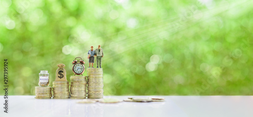 Fototapeta Saving for retirement and pension fund concept : Senior retired couple, vintage clock, US dollar money bag, deposit saving jar on steps of rising coins, depicts long-term investment for aging society obraz
