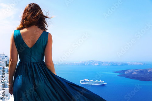 Beautiful woman in dress in front of  architecture of Santorini island, Greece. Europe travel vacation.