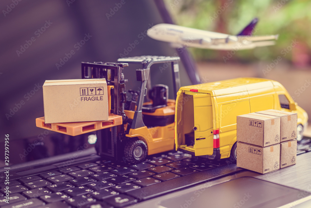 Fototapeta Logistics, supply chain and delivery service concept : Fork-lift truck moves a pallet with box carton. Van on a laptop computer, depicts wide spread of products around globe in ecommerce popular era