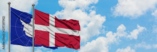 Photo Antarctica and Denmark flag waving in the wind against white cloudy blue sky together