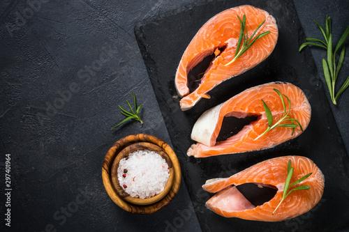 Fototapeta  Raw salmon steak on black top view.