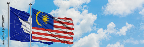 Photo Antarctica and Malaysia flag waving in the wind against white cloudy blue sky together