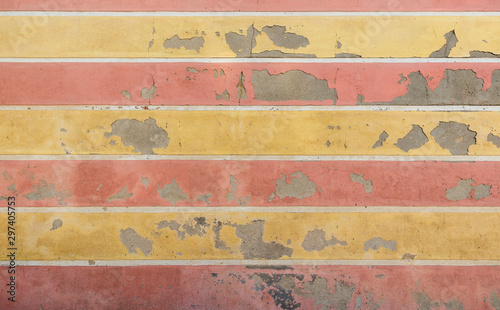 Fotografering  Weathered and old concrete wall with horizontal yellow and red stripes, paint is peeling off