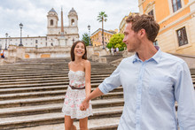 Happy Romantic Couple Holding Hands On Spanish Steps In Rome, Italy. Joyful Young Interracial Couple Walking On The Travel Landmark Tourist Attraction On Romance Europe Holiday Vacation.