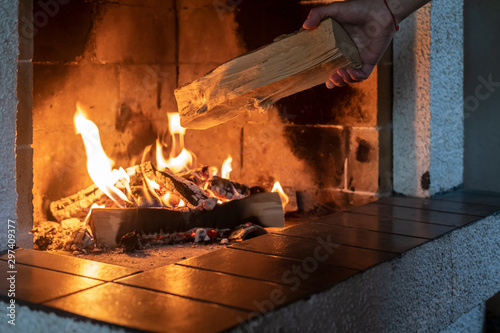 Hands put firewood in a kindled fireplace on a cold winter day Fototapete