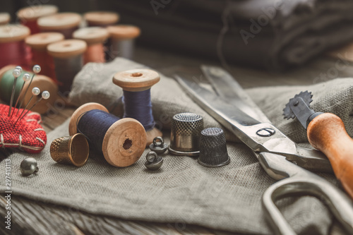Obraz na plátne Retro sewing items: tailoring scissors, cutting knife, thimble, wooden thread spools, cushion for including pins, fabrics and sewing accessories