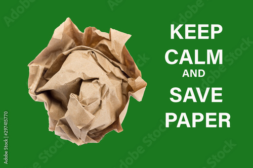 crumpled into a lump craft paper isolated on green background with inscription keep calm and save paper, forest conservation concept