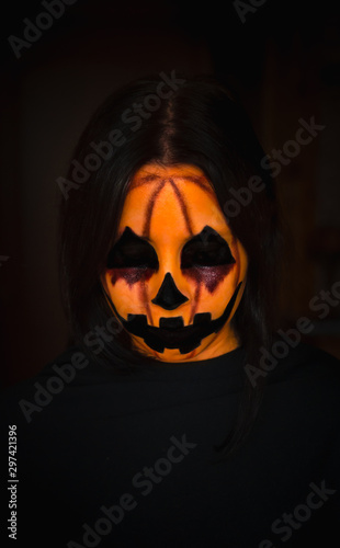 Creepy halloween pumpkin monster face with closed eyes on black background Wallpaper Mural