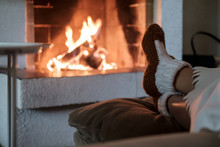Female Legs In Woolen Socks, Covered With White Blanket On The Background Of The Open Fireplace With Lighted Fire Wood. Relaxation, Warmth And Comfort In The House In The Winter Evening.