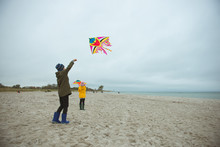 Teen Brother And Sister Playing With Kites In Sand Dunes Of Baltic Coastline