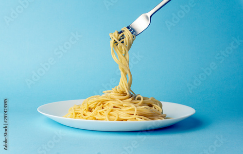 Spaghetti pasta with a fork on a white plate on a blue background. Creative, minimal concept