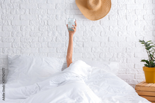 Obraz Young woman with glass of water lying in bed - fototapety do salonu