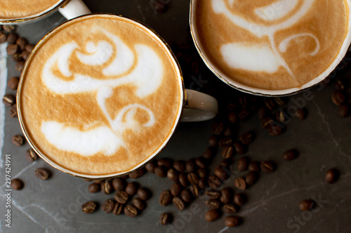 Tuinposter Cafe close-up of a flower drawing on coffee, latte art on a background of coffee beans on a table