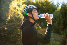 Female Cyclist Drinking Water ...