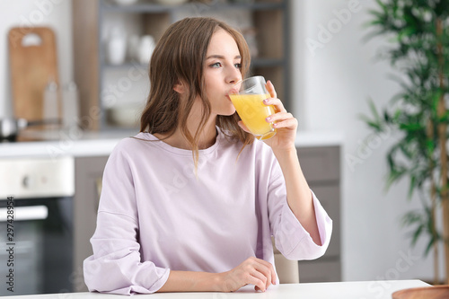 Poster Sap Beautiful young woman drinking orange juice in kitchen