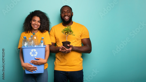 Aluminium Prints Akt Happy couple hold a plastic container and a small tree over a light blue color. Concept of forestation, ecology, conservation, recycling and sustainability