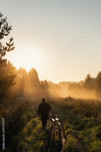Papiers peints Chasse Vintage hunter walks the forest road. Rifle Hunter Silhouetted in Beautiful Sunset or Sunrise. Hunter aiming rifle in forest