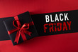 canvas print picture - Top view of black christmas boxes with red ribbon on black background with copy space for text. black Friday and Boxing Day composition.