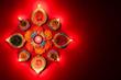 Leinwanddruck Bild - Happy Diwali - Clay Diya lamps lit during Dipavali, Hindu festival of lights celebration. Colorful traditional oil lamp diya on pink background