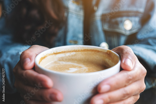 Fototapeta Closeup image of a woman holding a cup of hot latte coffee on the table
