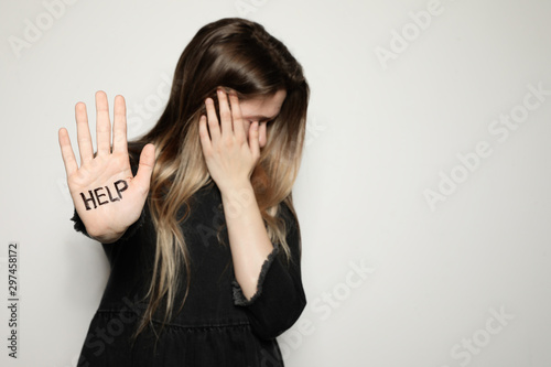 Fototapeta Young woman with word HELP written on her palm against light background, focus on hand