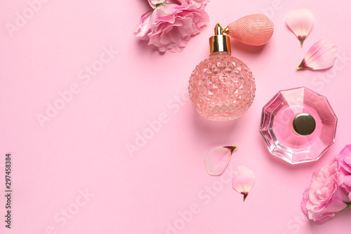 Flat lay composition with perfume bottles and flowers on light pink background, space for text