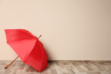 Colorful Umbrella On Floor Against Beige Wall. Space For Text