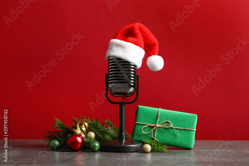 Photo Stands Amsterdam Microphone with Santa hat and decorations on grey table against red background. Christmas music