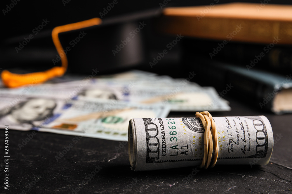 Fototapety, obrazy: Dollar banknotes, student graduation hat and books on black table. Tuition fees concept