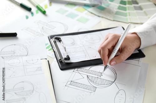 Obraz na plátně Female designer working at wooden table, closeup