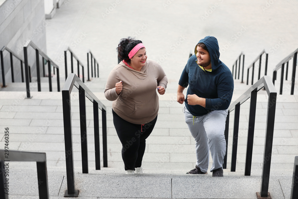 Fototapety, obrazy: Overweight couple running up stairs together outdoors
