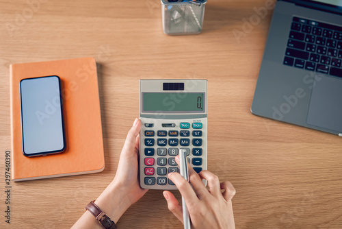 Fotomural  Woman holding and press calculator to calculate income expenses and plans for spending money on home office