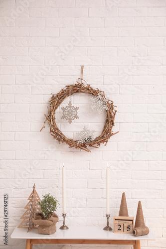 Console table with Christmas decoration near brick wall. Idea for festive interior