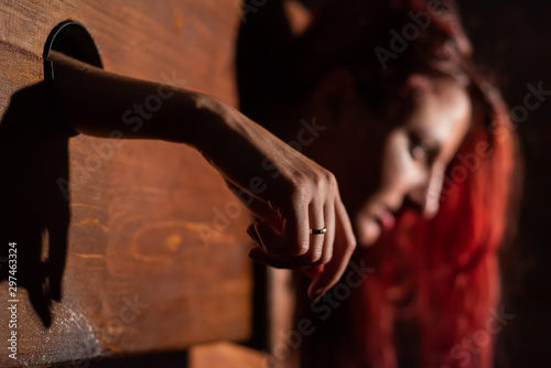 A redhead woman is imprisoned in a wooden pillory during sex games Wallpaper Mural