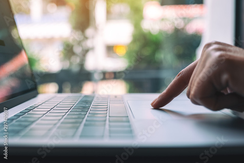 Fototapety, obrazy: Closeup image of a woman pressing finger on laptop computer touchpad