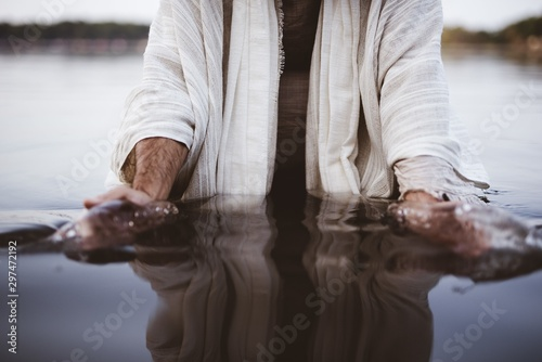 Closeup shot of a male wearing a biblical robe with his hands gathering water Fototapeta