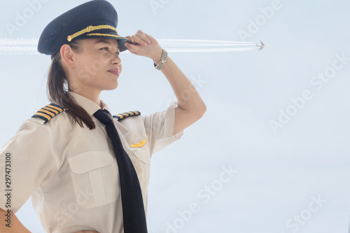 Photo A female captain pilot standing next to an airplane at the airport