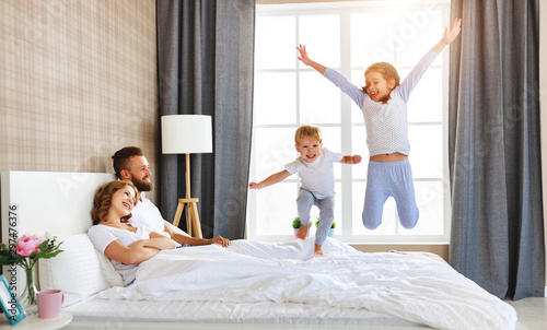 Fotomural  happy family mother, father and children laughing, playing and jumping in bed