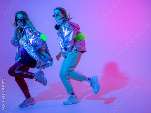 Photo Young stylish girls dancing in the Studio on a colored neon background
