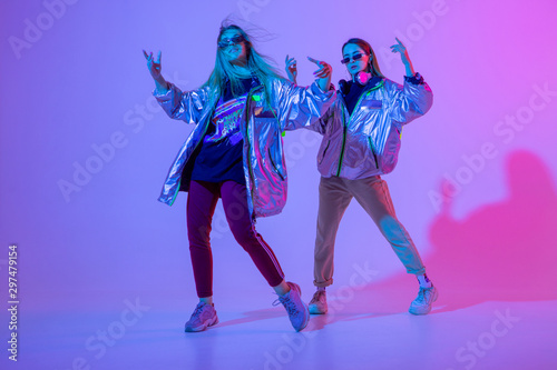Fototapeta  Young stylish girls dancing in the Studio on a colored neon background