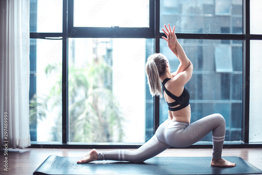 Fototapety, obrazy: Young woman practicing yoga in  gray background.Young people do yoga indoor at home.