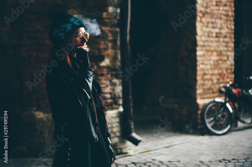 Obraz Red-haired girl in orange sunglasses smoking cigarette. Swag style girl. - fototapety do salonu