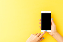 Woman's Hands Using Mobile Phone With Empty Screen On Yellow Background. Top View