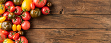 Various Kinds Of Tomatoes On Rustic Wooden Table With Copyspace. Food Background. Top View. Banner