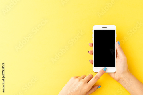 Obraz Woman's hands using mobile phone with empty screen on yellow background. Top view - fototapety do salonu