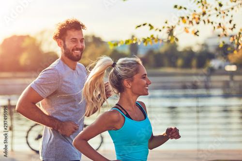 Carta da parati  Modern woman and man jogging / exercising in urban surroundings near the river