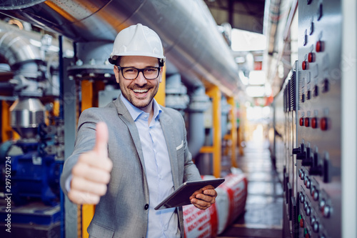 Fototapeta Successful caucasian supervisor in suit and with helmet holding tablet and showing thumbs up while standing next to dashboard in power plant. obraz