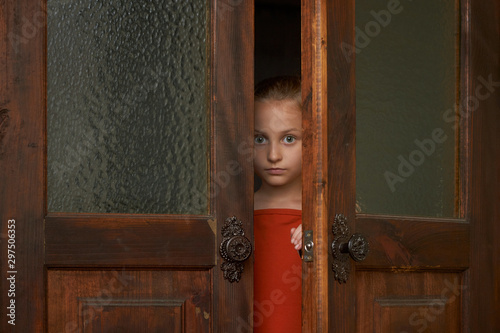 Photo A little scared girl is looking through the door slit
