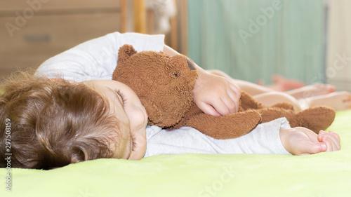 Vászonkép Caucasian girl boy 1 year old sleeping tingling brown teddy bear